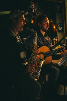 Free Two Men Playing Saxophone And Acoustic Guitar During Night Time Stock Images - 106240414