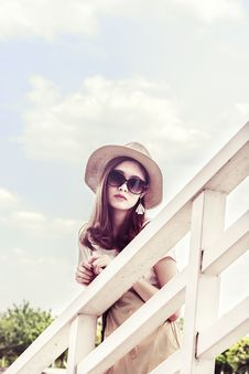 Free Woman Wearing Gray Sun Hat In Front Of White Fence Royalty Free Stock Photos - 106306408