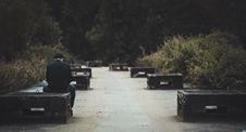Free Man In Black Dress Shirt With Blue Denim Shirt Sitting On Black Concrete Bench Near Green Plants Stock Photography - 106364112