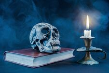 Free Gothic Skull On Old Book And Candle In Candlestick On Dark And Smoked Background Royalty Free Stock Images - 106507949
