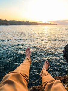 Free Person Wearing Yellow Pants Sitting On Rock Surrounded By Sea Stock Images - 108798614
