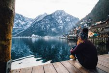 Free Woman In Purple Sweater Sitting On Wooden Floor With View Of Lake And Mountains Royalty Free Stock Image - 108798756