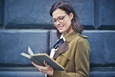 Free Woman In Brown Suede Peacoat Reading A Book Stock Images - 108798864