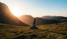 Free Silhouette Photography Of Person Standing On Green Grass In Front Of Mountains During Golden Hour Stock Photo - 108798990