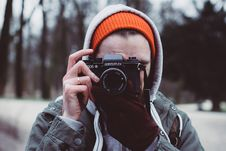 Free Man Wearing Gray Hooded Jacket Holding Black Camera Royalty Free Stock Photography - 108799347