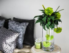 Free Clear Glass Vase With Green Flowers On Brown Wooden End Table Stock Photo - 108847580