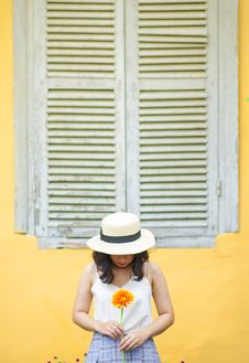 Free Woman In White Tank Top Holding Sunflower Near Window Outdoors Stock Photo - 108847590