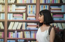 Free Woman Wearing V-neck Sleeveless Top Near Bookshelf Royalty Free Stock Image - 108922946