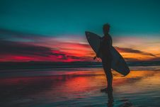 Free Silhouette Of Man In Wet Suit Holding White Surfboard While Standing On Beach During Golden Hour Stock Image - 108995621