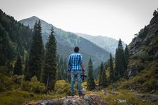 Free Man In Blue And White Checked Quarter-sleeved Shirt Holding Black Camera Standing On Rock Stock Photography - 109103242