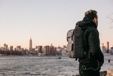 Free Man Wearing Black Bubble Jacket And Black Leather Backpack Near Bay Royalty Free Stock Photo - 109103255