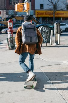 Free Man Wearing Brown Jacket, Blue Denim Jeans, And White Shoes Riding Skateboard On Sideway Royalty Free Stock Photos - 109360778