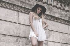 Free Woman In White Sleeveless Dress And Hat Near Wall Stock Images - 109434094