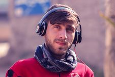 Free Closeup Photo Of A Man Wearing Red Top, Gray Scarf, And Black Beats By Dr. Dre Headphones Royalty Free Stock Images - 109434109