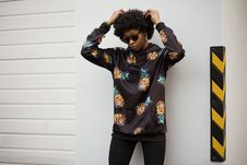 Free Photo Of A Woman In Pineapple Print Pullover Leaning On White Wall Royalty Free Stock Image - 109635436
