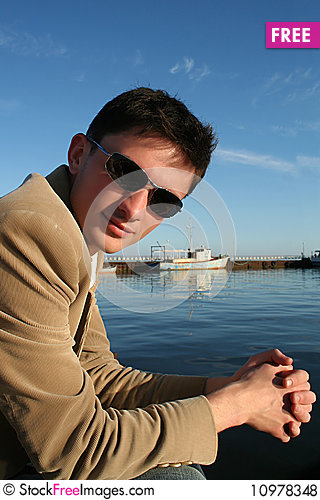 Young caucasian man sitting on a pier Stock Photo