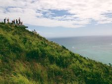 Free People Standing On A Green Mountain Peak Watching The Clear Blue Body Of Water Stock Image - 109883901