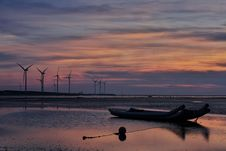 Free Windmills Behind Canoe Boat During Sunset Stock Photos - 109885423