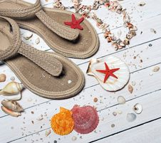Free Beige Thong Flat Sandals Placed Beside Seashells Royalty Free Stock Image - 109885526