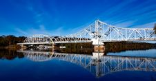 Free White Bridge Above Body Of Water Creating A Reflection Under White Clouds Stock Image - 109885531