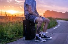 Free Man Sitting On Luggage On Road Side During Sunset Royalty Free Stock Image - 109885676