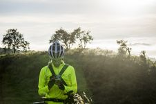 Free Man In Green Bicycle Suit Standing While Using His Smartphone Royalty Free Stock Photos - 109885678