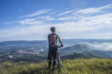 Free Biker Holding Mountain Bike On Top Of Mountain With Green Grass Stock Photo - 109885800