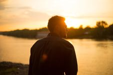 Free Man Sitting Near Large Body Of Water Under Clear Sky During Sunset Stock Image - 109886101