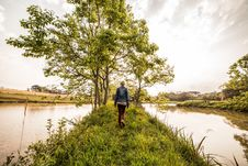Free Person In Blue Denim Jacket And Brown Pants Standing On Green Grass In Front Green Leaved Trees Between River Under Sunny Sky Stock Images - 109887404