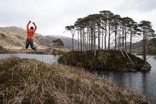 Free Man In Orange Long-sleeved Shirt Jumping On Lake Near Tall Trees At Daytime Royalty Free Stock Photos - 109896218