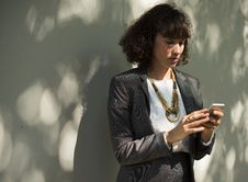 Free Woman In Black Blazer Holding A Smartphone While Standing Near Wall Stock Photography - 109904022