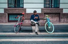 Free Person Sitting On Bench Between Two Road Bikes Royalty Free Stock Photography - 109904187