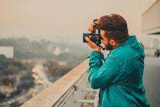 Free Man In Teal Button-Up Long Sleeved Shirt Shooting Using DSLR Camera Royalty Free Stock Photos - 109905058