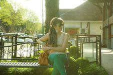 Free Woman In Brown Tank Top Sitting On Black Bench Beside Tree Stock Photography - 109907372