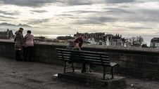 Free Woman Taking Photo While Sitting On The Bench Behind The Building Scenery Stock Photos - 109907483