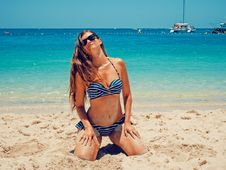 Free Woman In Blue And White Bikini Kneeling On Sand Stock Photography - 109907502