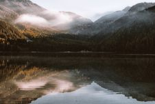 Free Mountain Reflection On Body Of Water Under White Sky At Royalty Free Stock Images - 109907669