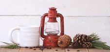 Free Red Kerosene Lantern Beside White Ceramic Mug On Brown Wooden Table Royalty Free Stock Photo - 109907795