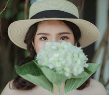 Free Woman Wearing White Hat Holding Flowers Stock Photos - 109908423