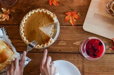 Free Person Holding Knife And Fork Cutting Slice Of Pie On Brown Wooden Table Royalty Free Stock Images - 109908569