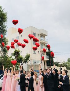 Free Women Wearing Pink Dresses And Men Wearing Black Suit Jacket And Pants Raising Hands With Red Heart Balloons Stock Images - 109908624