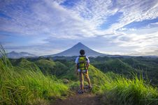 Free Man Wearing White Shirt, Brown Shorts, And Green Backpack Standing On Hill Stock Photo - 109908700