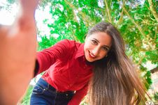 Free Smiling Woman In Red Shirt And Blue Jeans Taking Selfie Under Green Leaved Tree Stock Images - 109908714