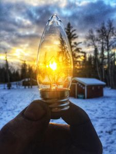 Free Person Holding Led Bulb In Front Of Sunrise Photo Royalty Free Stock Images - 109908829