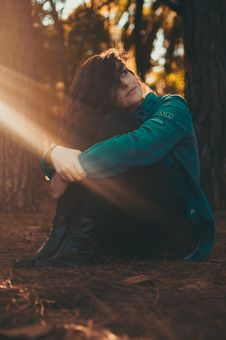 Free Selective Focus Photography Of Woman In Green Jacket And Black Pants Sitting On Field Surrounded With Trees Royalty Free Stock Images - 109908969