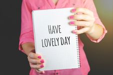 Free Woman Wearing Pink Dress Holding Graphing Notebook With Have A Lovely Day Sign Royalty Free Stock Image - 109909416
