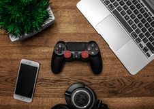 Free Silver Macbook Beside Black Sony Ps4 Dualshock 4, Silver Iphone 6, And Round Black Keychain On Brown Wooden Table Royalty Free Stock Images - 109909569