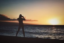 Free Silhouette Of Woman Holding Camera Near Seashore During Golden Hour Stock Photo - 109909620