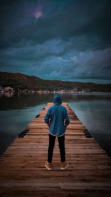 Free Man Wearing Blue Hoodie Standing On Wooden Dock Stock Photo - 109909790