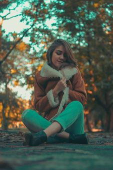 Free Woman Wearing Brown-and-white Coat And Teal Denim Jeans Sitting On Road Surface Royalty Free Stock Photo - 109909865